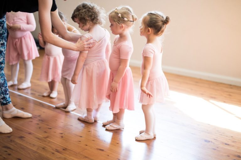 row-of-small-girl-children-dressed-in-pink-ballet-tutu-stockings-shoes-slippers-in-a-line-taking-a_t20_E0VGaZ
